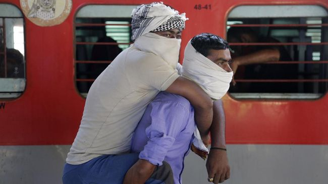 Migrant worker Hira Ali carries his physically disabled brother Muslim Ali on his back as they wait to board a special train to return to Agra in Uttar Pradesh state, during a nationwide lockdown to curb the spread of new coronavirus, at a railway station in Ahmedabad, in the western Indian state of Gujarat, Saturday, May 2, 2020. India on Friday ran the first train service for thousands of migrant workers desperate to return home since it imposed a nationwide lockdown to control the spread of the coronavirus. Several states, including Rajasthan, Jharkhand, Bihar, Kerala, Maharashtra, Uttar Pradesh, Punjab and Telangana have demanded special trains for returning workers because they couldn't arrange enough buses. Around 1 million migrant workers from Uttar Pradesh are still stranded in other Indian states, state government spokesman, Awanish Awasthi said. (AP Photo/Ajit Solanki)