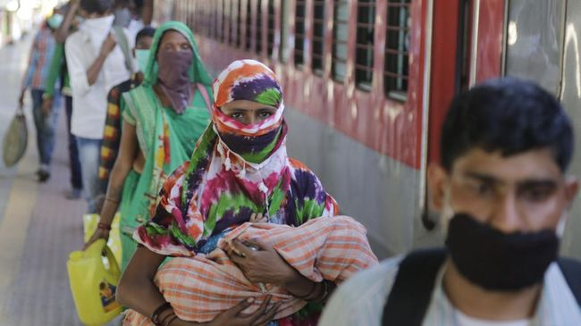 Migrant workers stand to board a special train to return to Agra in Uttar Pradesh state, during a nationwide lockdown to curb the spread of new coronavirus, at a railway station in Ahmedabad, in the western Indian state of Gujarat, Saturday, May 2, 2020. India on Friday ran the first train service for thousands of migrant workers desperate to return home since it imposed a nationwide lockdown to control the spread of the coronavirus. Several states, including Rajasthan, Jharkhand, Bihar, Kerala, Maharashtra, Uttar Pradesh, Punjab and Telangana have demanded special trains for returning workers because they couldn't arrange enough buses. Around 1 million migrant workers from Uttar Pradesh are still stranded in other Indian states, state government spokesman, Awanish Awasthi said. (AP Photo/Ajit Solanki)