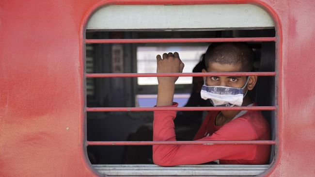 A migrant workers sits inside a special train to return to Agra in Uttar Pradesh state, during a nationwide lockdown to curb the spread of new coronavirus, at a railway station in Ahmedabad, in the western Indian state of Gujarat, Saturday, May 2, 2020. India on Friday ran the first train service for thousands of migrant workers desperate to return home since it imposed a nationwide lockdown to control the spread of the coronavirus. Several states, including Rajasthan, Jharkhand, Bihar, Kerala, Maharashtra, Uttar Pradesh, Punjab and Telangana have demanded special trains for returning workers because they couldn't arrange enough buses. Around 1 million migrant workers from Uttar Pradesh are still stranded in other Indian states, state government spokesman, Awanish Awasthi said. (AP Photo/Ajit Solanki)