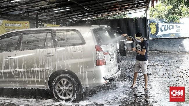 Tempat cuci mobil incarwash di Jalan Tb. Simatupang tetap mendahulukan peraturan pemerintah dengan menjaga rantai penyebaran virus Covid 19, dengan aturan ketat terhadap pelanggan dan pegawai, dengan menggunakan masker dan pelindung wajah (Face Shield) serta pelanggan tidak boleh turun dari mobil saat proses pencucian berlangsung. Jakarta.  Selasa (5/5/2020). CNN Indonesia/Andry Novelino