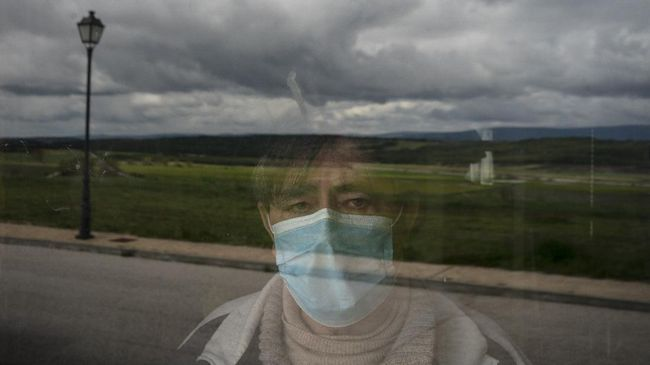 In this April 28, 2020 photo, Eusebio Soria poses for a photo behind a glass door at the entrance of his home as he recovers from the new coronavirus in Cabrejas del Pinar, Spain, in the province of Soria. Soria said that at first his doctor diagnosed him with the flu until his fever wouldn't go away and he was sent to the hospital where he spent 11 days after being tested positive for the coronavirus. Many in Spain's small and shrinking villages thought their low populations would protect them from the coronavirus pandemic. The opposite appears to have proved true. Soria, a north-central province that's one of the least densely peopled places in Europe, has recorded a shocking death rate. Provincial authorities calculate that at least 500 people have died since the start of the outbreak in April. (AP Photo/Felipe Dana)