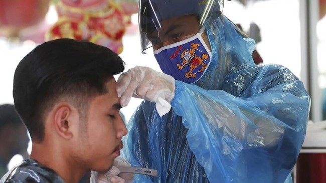A barber wearing a face mask to protect against the new coronavirus shaves a customer at a barbershop in Jakarta, Indonesia, Friday, May 1, 2020. (AP Photo/Achmad Ibrahim)