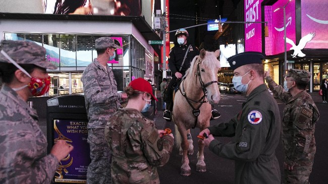 In this Saturday, May 2, 2020 photo, a mounted New York City police officer wearing a mask greets visiting Air Force officers in New York during the coronavirus pandemic. (AP Photo/Mark Lennihan)