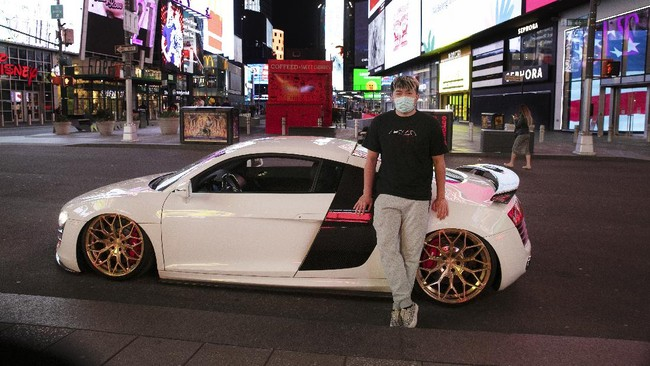 In this Saturday, May 2, 2020 photo, Danny Lin poses for photos with his 2008 Audi R8 in New York's Times Square during the coronavirus pandemic.