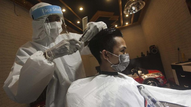 Seorang tukang pangkas rambut menggunakan alat pelindung diri (APD) saat mencukur rambut pelanggannya di Jalan Patih Rumbih, Palangkaraya, Kalimantan Tengah, Jumat (1/5/2020). Menurut pemilik salon, penggunaan APD tersebut sebagai antisipasi terhadap penyebaran COVID-19 serta membuat pelanggan merasa nyaman saat menggunakan jasanya. ANTARA FOTO/Makna Zaezar/wsj.