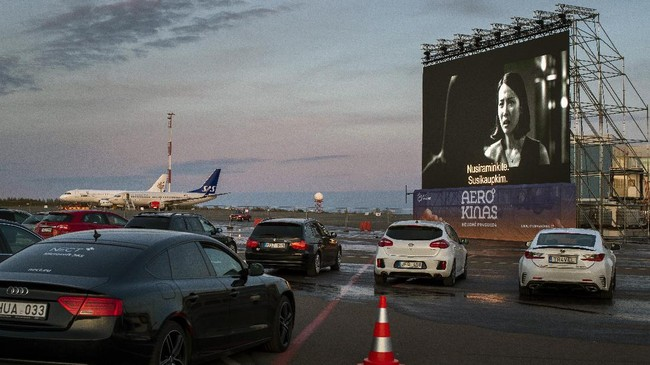 People sit in their cars watching a movie at a new drive-in cinema on a airport apron area, where the planes take off and land, in Vilnius, Lithuania, as regular theaters are closed due to the coronavirus outbreak on Wednesday, April 29 2020. For the first time in history of the Vilnius airport, a drive-in cinema start has been operating in the airport apron area. For the moment, the airport, which had been growing and adding new destinations, is quiet and waiting for international travel restrictions to be lifted. The drive-in cinema will operate one month, starting on April 29th. (AP Photo/Mindaugas Kulbis)