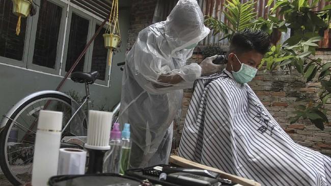 Seorang tukang cukur menggunakan Alat Pelindung Diri (APD) ketika memotong rambut di halaman rumah pelanggan, di Pekanbaru, Riau, Kamis (9/4/2020). Sepinya pengunjung yang datang ke barbershop membuat pelaku usaha potong rambut menerima jasa panggilan cukur ke rumah dengan menggunakan pakaian pelindung untuk pencegahan penularan virus Corona (COVID-19). ANTARA FOTO/Rony Muharrman/aww.