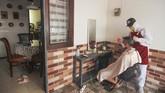 Seorang tukang cukur menggunakan Alat Pelindung Diri (APD) saat memotong rambut di halaman rumah pelanggan di Kelapa Dua, Depok, Jawa Barat, Senin (27/4/2020). Penerapan Pembatasan Sosial Berskala Besar (PSBB) Kota Depok membuat Pelaku usaha cukur rambut tersebut menerima jasa panggilan cukur ke rumah dengan menggunakan APD sebagai upaya pencegahan virus corona (COVID-19). ANTARA FOTO/Asprilla Dwi Adha/hp.