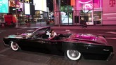 In this Saturday, May 2, 2020 photo, Tina Singh relaxes in a friend's 1967 Lincoln Continental in New York's Times Square during the coronavirus pandemic. Car mavens normally wouldn't dare rev their engines in Midtown, but now they're eagerly driving into the city to take photos and show off for sparse crowds walking through the commercial hub. (AP Photo/Mark Lennihan)