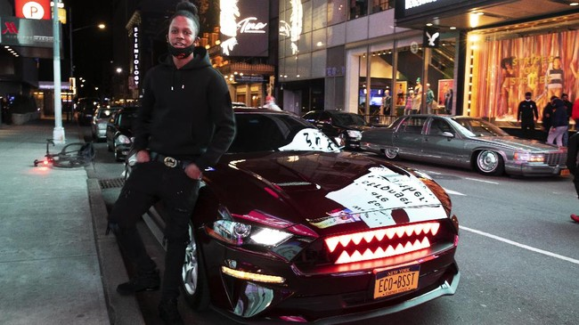 In this Saturday, May 2, 2020 photo, Andre Godfrey poses with his 2018 Ford Mustang EcoBoost - - with glowing red shark teeth embedded in the grill - - in New York's Times Square during the coronavirus pandemic. Car mavens normally wouldn't dare rev their engines in Midtown, but now they're eagerly driving into the city to take photos and show off for sparse crowds walking through the commercial hub. (AP Photo/Mark Lennihan)