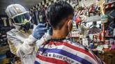 Seorang tukang cukur mengunakan alat pelindung diri (APD) saat mencukur rambut pelanggannya di tempat pangkas rambut Chemot Barbershop, Ciawi, Bogor, Jawa Barat, Sabtu (4/4/2020). Penggunaan APD tersebut merupakan sosialisasi kepada pelanggan serta sebagai antisipasi agar lebih waspada terhadap penularan COVID-19. ANTARA FOTO/Yulius Satria Wijaya/hp.