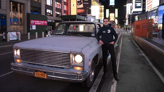 In this April 29, 2020 photo, Mike Hodurski poses with his 1977 Chevy pickup in New York's Times Square during the coronavirus pandemic.