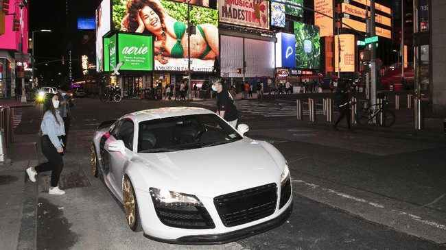 In this Saturday, May 2, 2020 photo, Claudia Luong, left, and Danny Lin hop into his 2008 Audi R8 for a spin around New York's Times Square during the coronavirus pandemic. Car mavens normally wouldn't dare rev their engines in Midtown, but now they're eagerly driving into the city to take photos and show off for sparse crowds walking through the commercial hub. (AP Photo/Mark Lennihan)