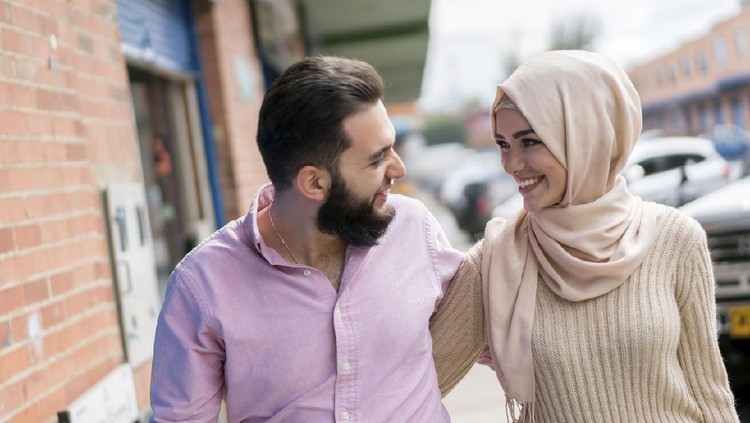 Portrait of a loving young Muslim couple smiling on the street - lifestyle concepts
