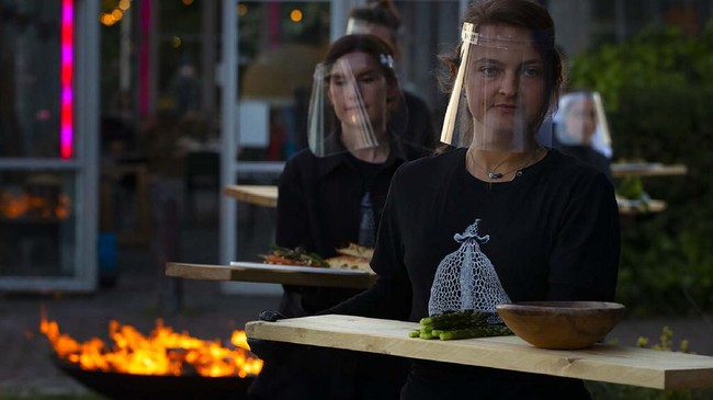 Staff at the Mediamatic restaurant serve food to volunteers seated in small glasshouses during a try-out of a setup which respects social distancing abiding by government directives to combat the spread of the COVID-19 coronavirus in Amsterdam, Netherlands, Tuesday, May 5, 2020. (AP Photo/Peter Dejong)