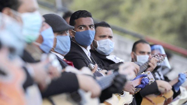 Several of the city's mariachi groups, all of them wearing masks against the spread of the new coronavirus, perform together in an appeal to the authorities to allow them to work this upcoming Sunday during Mother's Day, at the Tribuna del Sur grandstand in Quito, Ecuador, Tuesday, May 5, 2020. The mariachis have not been able to perform and earn a living since the lockdown imposed by the government in an attempt to slow down the spread of COVID-19 disease. (AP Photo/Dolores Ochoa)