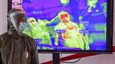 Petugas medis mengamati monitor alat deteksi suhu tubuh atau