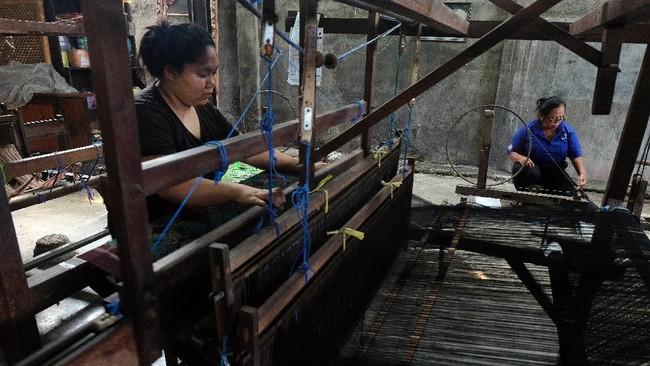 Perajin menyelesaikan pembuatan kain Endek menggunakan alat tenun bukan mesin (ATBM).ANTARA FOTO/Nyoman Hendra Wibowo