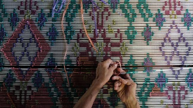 Perajin mengikat benang sesuai motif sebelum proses pewarnaan. ANTARA FOTO/Nyoman Hendra Wibowo