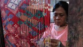Perajin melakukan proses pewarnaan motif pada benang. ANTARA FOTO/Nyoman Hendra Wibowo