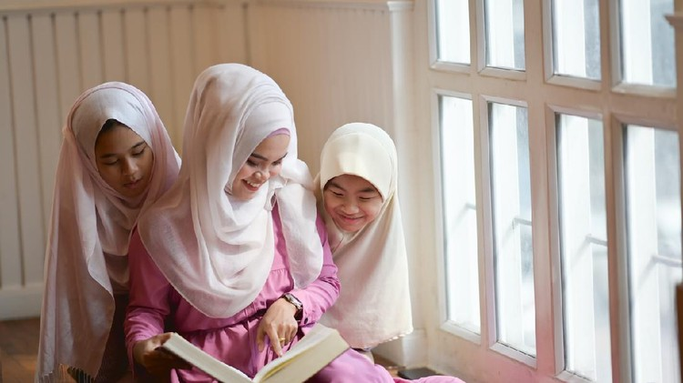 Young Asian Muslim teaching her sister to reading a book