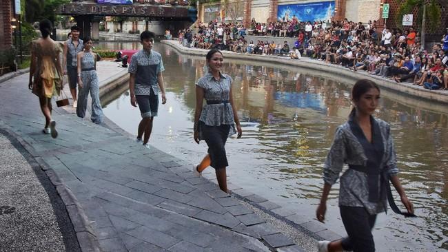 Sejumlah model dari kaum milenial memperagakan rancangan busana berbahan kain Endek dalam Denpasar Fashion Festival di pedestrian sungai Taman Kumbasari, Denpasar. ANTARA FOTO/Nyoman Hendra Wibowo