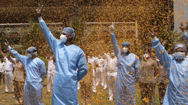 An Indian Air Force helicopter showers flower petals on the staff of INS Asvini hospital in Mumbai, India, Sunday, May 3, 2020. The event was part the Armed Forces' efforts to thank the workers, including doctors, nurses and police personnel, who have been at the forefront of the country's battle against the COVID-19 pandemic. (AP Photo/Rajanish Kakade)
