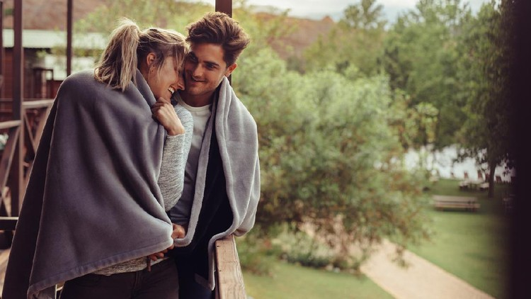 Loving man and woman standing in their hotel room balcony wrapped in blanket. Romantic couple in a blanket standing together on a winter holiday.