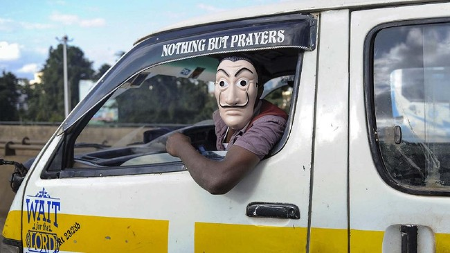A passenger wears a mask as he travels in a public minibus, known locally as a matatu, on a street in Nairobi, Kenya Wednesday, May 6, 2020. It is a legal requirement in Kenya for all passengers in public or private vehicles to wear a mask covering the mouth and nose. (AP Photo/John Muchucha)