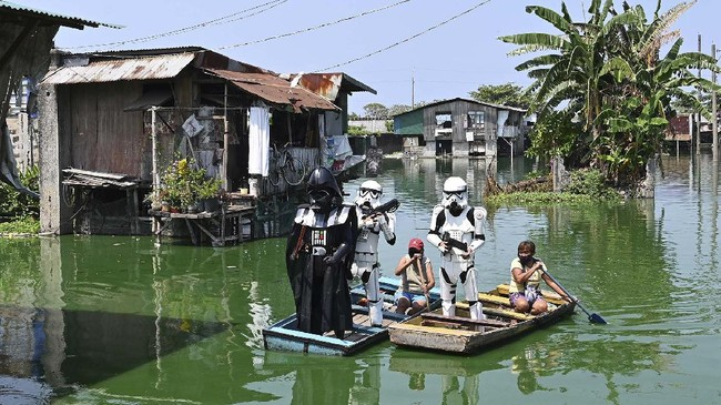 Local youth representatives dressed Stormtroopers and Darth Vader (L-in black) from the Star Wars film franchise patrol in a wooden boat around a submerged village to remind residents to stay at home during the enhanced community quarantine in suburban Manila on May 6, 2020, as part of government's efforts to combat the spread of the COVID-19 coronavirus. (Photo by Ted ALJIBE / AFP)