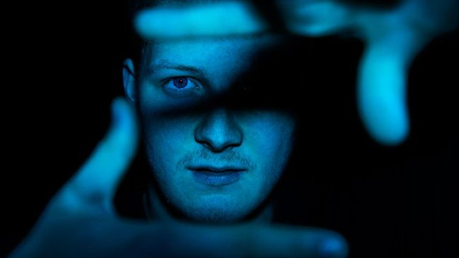 Eye Contact Youth Portrait. Young teenage man showing picture frame with his hands towards the camera. Illuminated in blue light. Young People Teenage Lifestyle Portrait.