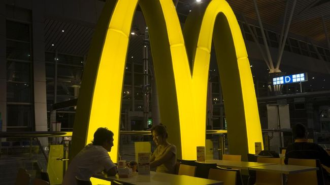 Kuching, Malaysia - October 3, 2010: Smiling asian couple eating in the McDonalds restaurant of the International airport of Kuching. It is dark, and the illuminated M-Logo of McDonalds  is shining on the tables.