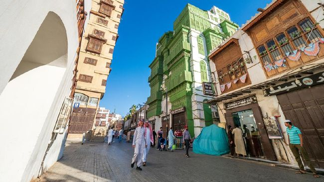 December 7th 2019, Jeddah, Saudi Arabia: The whole area (next to the green Noorwali House) was recently renovated and forms the main attraction of the old Jeddah nowadays. Many people (including two Saudi men in traditional clothes) are strolling along this street, as it leads into the Souk Baab Makkah, the traditional vegetable souk in Jeddah.