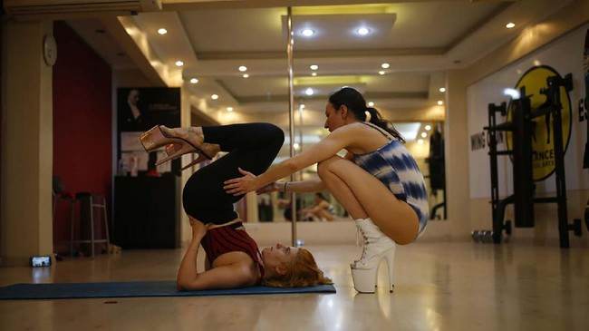 In this Thursday, April 30, 2020 photo, Tuba Parlak, 39, right, a pole dancing performer and instructor, makes an online training session for students at home, with her assistant and trainee Aybuke Yanar, 21, at her studio in Istanbul. To stem the spread of COVID-19, Turkey closed down sports facilities in March but Parlak's students wanted to continue their pole lessons. Using video conferencing, Parlak teaches the vigorous exercise from her studio in Istanbul's hip Cihangir district. (AP Photo/Emrah Gurel)