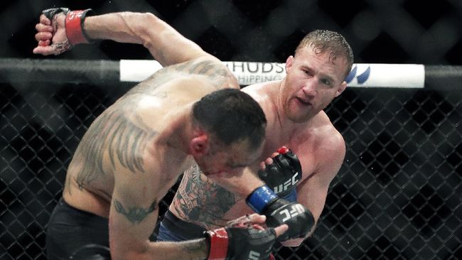 Tony Ferguson, left, falls backward after taking a punch from Justin Gaethje during a UFC 249 mixed martial arts bout, early Sunday, May 10, 2020, in Jacksonville, Fla. (AP Photo/John Raoux)