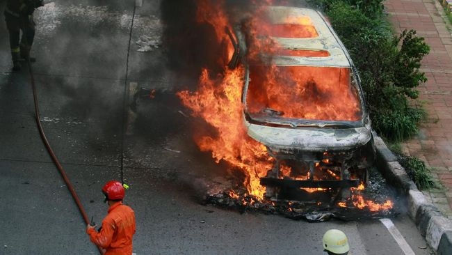 Petugas Sudin pemadam kebakaran Jakarta Selatan mencoba memadamkan api yang membakar mobil mewah jenis Toyota Vellfire di Jalan Sultan Iskandarsyah, Pondok Indah, Jakarta, Senin (11/5/2020). Api yang membakar mobil mewah tersebut diduga berasal dari korsleting arus listrik mobil dan tidak ada korban jiwa dalam peristiwa tersebut. ANTARA FOTO/Muhammad Iqbal/hp.