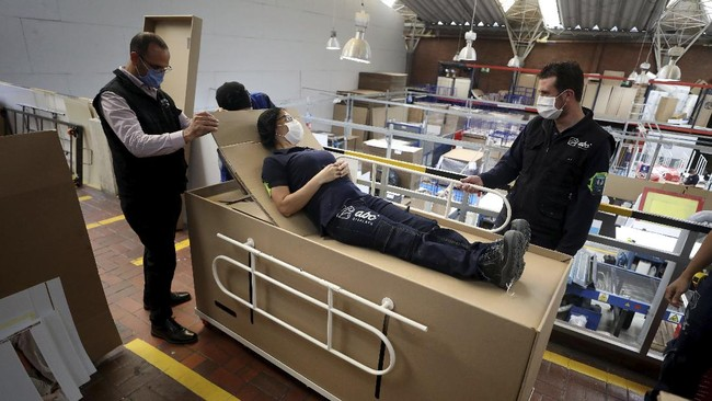 Rodolfo Gomez, left, and his employees demonstrate how their design of a cardboard box can serve as both a hospital bed and a coffin, designed for COVID-19 patients, in Bogota, Colombia, Friday, May 8, 2020. Gomez said he plans to donate the first units to Colombia's Amazonas state, and that he will sell others to small hospitals for 87 dollars. (AP Photo/Fernando Vergara)