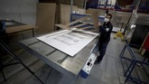 A worker at a company that designs packaging for product displays assembles a cardboard box designed to serve as both a hospital bed and a coffin, intended for COVID-19 patients, in Bogota, Colombia, Friday, May 8, 2020. Owner Rodolfo Gomez said he plans to donate the first units to Colombia's Amazonas state, and that the company will sell others to small hospitals for 87 dollars. (AP Photo/Fernando Vergara)