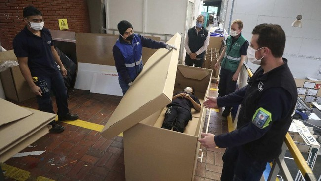 Rodolfo Gomez, to center, and his employees demonstrate how their design of a cardboard box can serve as both a hospital bed and a coffin, designed for COVID-19 patients, in Bogota, Colombia, Friday, May 8, 2020. Gomez said he plans to donate the first units to Colombia's Amazonas state, and that he will sell others to small hospitals for 87 dollars. (AP Photo/Fernando Vergara)