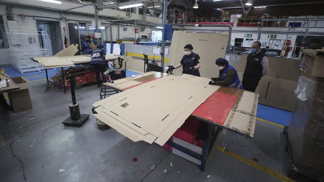 Workers at a company that designs packaging for product displays assemble a cardboard box designed to serve as both a hospital bed and a coffin, intended for COVID-19 patients, in Bogota, Colombia, Friday, May 8, 2020. Owner Rodolfo Gomez said he plans to donate the first units to Colombia's Amazonas state, and that the company will sell others to small hospitals for 87 dollars. (AP Photo/Fernando Vergara)