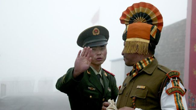 In this photograph taken on July 10, 2008, A Chinese soldier gestures as he stands near an Indian soldier on the Chinese side of the ancient Nathu La border crossing between India and China. When the two Asian giants opened the 4,500-metre-high (15,000 feet) pass in 2006 to improve ties dogged by a bitter war in 1962 that saw the route closed for 44 years, many on both sides hoped it would boost trade. Two years on, optimism has given way to despair as the flow of traders has shrunk to a trickle because of red tape, poor facilities and sub-standard roads in India's remote northeastern mountainous state of Sikkim. AFP PHOTO/Diptendu DUTTA (Photo by DIPTENDU DUTTA / AFP)