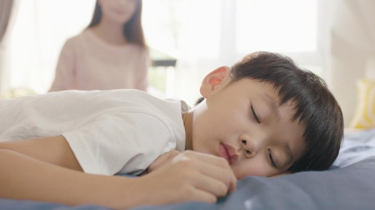 Asian boy sleeping in bed in the morning while mother sitting in background