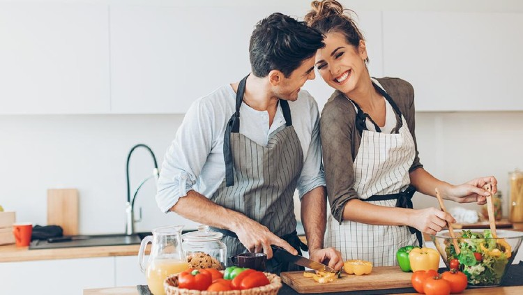 Lovely couple with fresh fruits and vegetables in the kitchen.