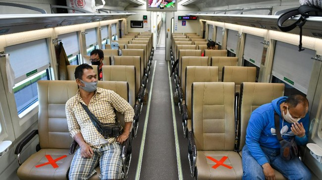 Sejumlah penumpang dengan mengenakan masker di dalam gerbong kereta api luar biasa relasi Gambir-Surabaya Pasar Turi lintas selatan di Stasiun Gambir, Jakarta, Selasa (12/5/2020). PT Kereta Api Indonesia (KAI) mengoperasikan kereta api luar biasa (KLB) jarak jauh untuk melayani penumpang yang dikecualikan sesuai aturan pemerintah dengan penerapan protokol pencegahan COVID-19 yang ketat hingga 31 Mei 2020 mendatang. ANTARA FOTO/M Risyal Hidayat/foc.