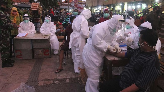 Petugas melakukan pemeriksaan cepat COVID-19 (Rapid Test) terhadap warga di Pasar Keputran, Surabaya, Jawa Timur, Selasa (12/5/2020). Pemeriksaan cepat terhadap sejumlah  pedagang dan buruh di pasar induk itu guna mengetahui kondisi kesehatan mereka serta untuk mencegah penyebaran virus Corona (COVID-19). ANTARA FOTO/Didik Suhartono/hp.