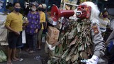 Petugas kepolisian yang mengenakan kostum menyeramkan 'Celuluk' melakukan sosialisasi langkah-langkah pencegahan COVID-19 di Pasar Tradisional Sempidi, Badung, Bali, Selasa (12/5/2020). Kegiatan yang dilakukan petugas kepolisian Polres Badung di sejumlah pasar tradisional dan ruas jalan tersebut dilakukan untuk mengimbau masyarakat terus melakukan berbagai upaya pencegahan penyebaran COVID-19 seperti mengenakan masker, rutin mencuci tangan, menjaga jarak serta tidak melakukan perjalanan mudik. ANTARA FOTO/Fikri Yusuf/foc.