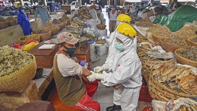 """Petugas kesehatan mengambil sampel darah seorang pedagang saat menggelar tes diagnostik cepat atau rapid test COVID-19 di Pasar Tradisional Mandalika, Bertais, Mataram, NTB, Senin (11/5/2020). Dinas Kesehatan Kota Mataram melakukan tes diagnostik cepat COVID-19 di pasar tersebut menyusul adanya salah satu pedagang yang meninggal dunia dengan status positif COVID-19 serta sebagai upaya """"contact tracing"""" atau penelusuran kontak untuk memutus penyebaran virus Corona. ANTARA FOTO/Ahmad Subaidi/wsj."""