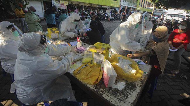 Petugas melakukan pemeriksaan cepat COVID-19 (Rapid Test) terhadap warga di Pasar Kembang, Surabaya, Jawa Timur, Rabu (13/5/2020). Pemeriksaan cepat terhadap sejumlah pedagang di pasar itu guna mengetahui kondisi kesehatan mereka sebagai upaya untuk mencegah penyebaran virus Corona (COVID-19). ANTARA FOTO/Didik Suhartono/foc.