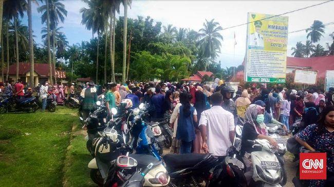 Ratusan warga berkerumun di luar pagar kantor Camat Sutera, Kabupaten Pesisir Selatan (Pessel), Sumatera Barat, Kamis (14/5). Mereka menunggu pembagian BLT dari pemkab setempat. HOLY ADIB
