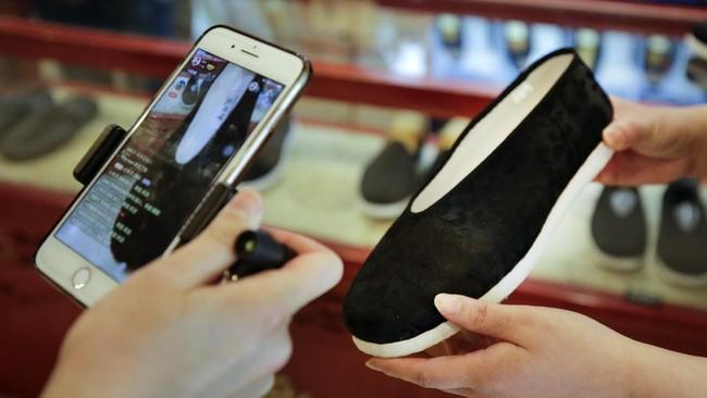 Salah satu pedagang sepatu di China menunjukkan sepatu yang dijual melalui live streaming. Penjual tersebut siaran langsung dari toko offline di Neiliansheng Footwear Beijing. (AP Photo/Andy Wong)